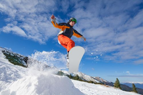 Man-jumping-with-snowboard-from-mountain-hill
